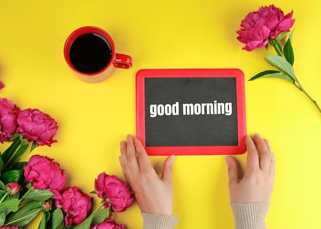 Zwei weibliche hände halten einen schwarzen kreiderahmen mit den wörtern guten morgen