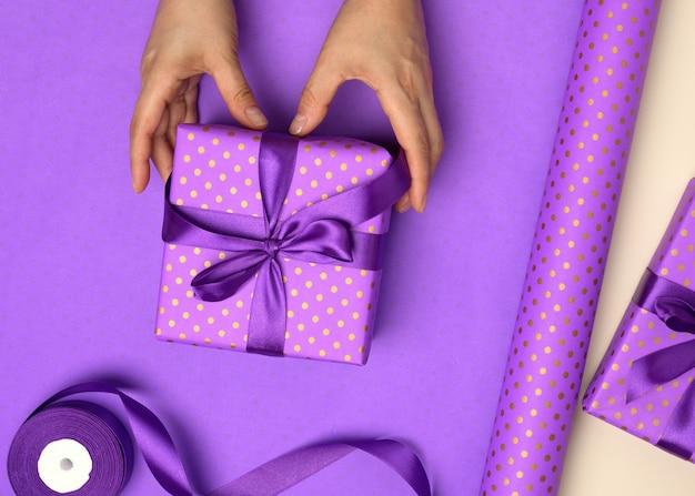 Zwei weibliche hände halten lila geschenkbox auf papierhintergrund, konzept der glückwünsche zum geburtstag, draufsicht