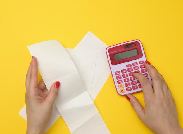 Zwei weibliche hände halten papierschecks und einen rosa taschenrechner auf gelbem grund. das konzept der berechnung des budgets, der ausgaben und der einnahmen des unternehmens und der familie, draufsicht