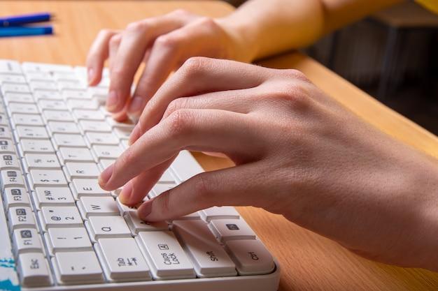 Zwei weibliche hand tippt auf einer weißen tastatur mit englischen buchstaben, nahaufnahme, selektiver fokus, seitenansicht fernlernkonzept