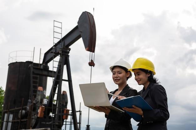 Zwei weibliche ingenieure stehen neben arbeitsölpumpen mit einem weißen himmel.