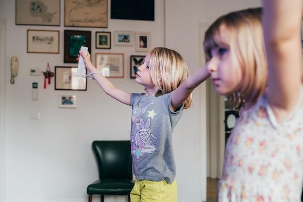 Zwei weibliche kinder, die einen joystick halten, der videospiel zu hause spielt