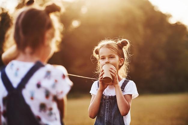 Zwei weibliche kinder stehen auf dem feld und sprechen mit einer schnur können telefonieren.