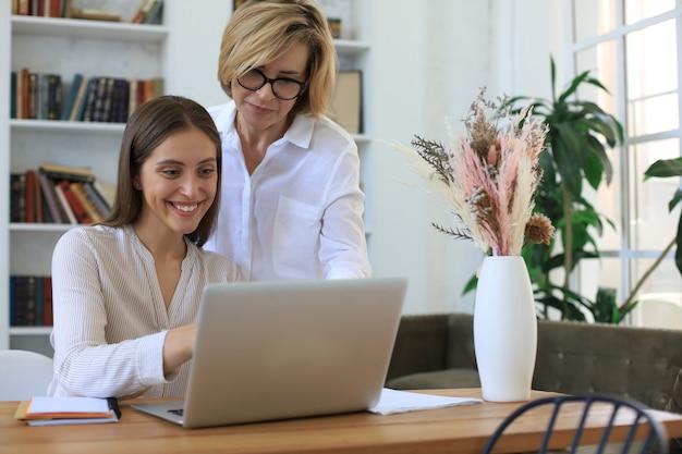 Zwei weibliche kollegen, die mit laptop arbeiten und ein neues projekt besprechen.