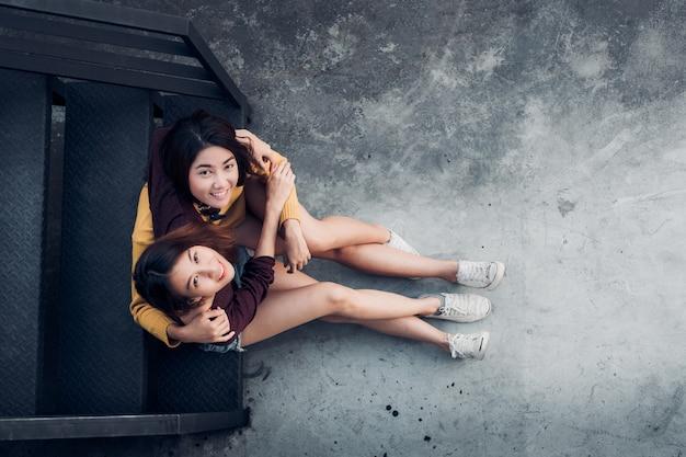 Zwei weibliche lesbische lgbt paare, die zusammen an der schwarzen dachspitzentreppenumarmung sitzen und oben schauen