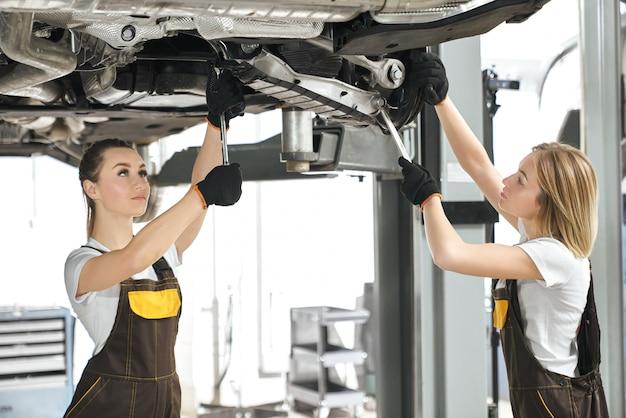 Zwei weibliche mechaniker, die fahrgestell des automobils reparieren