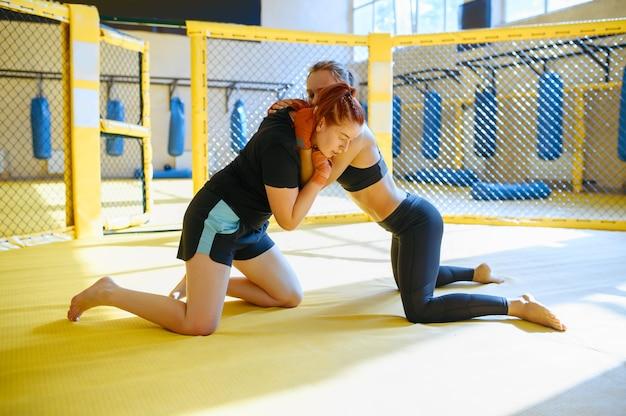 Zwei weibliche mma-kämpfer kämpfen in einem käfig im fitnessstudio.