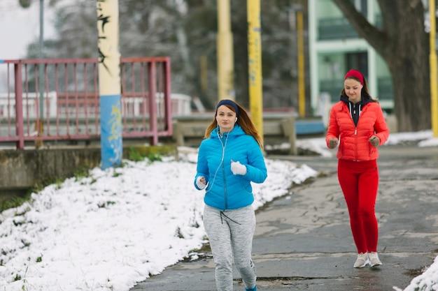 Zwei weibliche rüttler, die auf straße im winter laufen