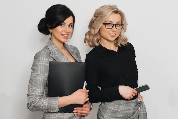 Zwei weibliche sekretärinnen auf hellem hintergrund