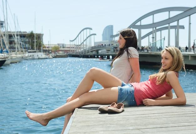 Zwei weibliche studenten in kurzen hosen sittng auf dem liegeplatz