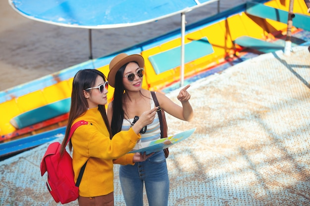 Zwei weibliche touristen halten eine karte, um orte zu finden.