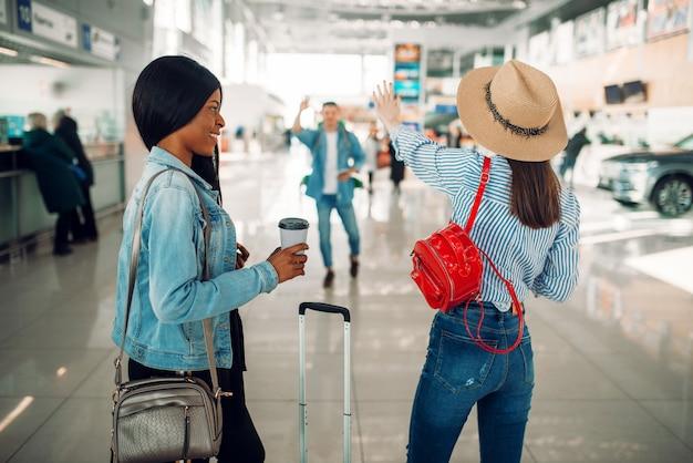 Zwei weibliche touristen mit fällen treffen eine freundin am flughafen. passagiere mit gepäck im flugterminal