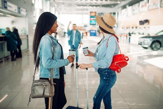 Zwei weibliche touristen treffen eine freundin am flughafen