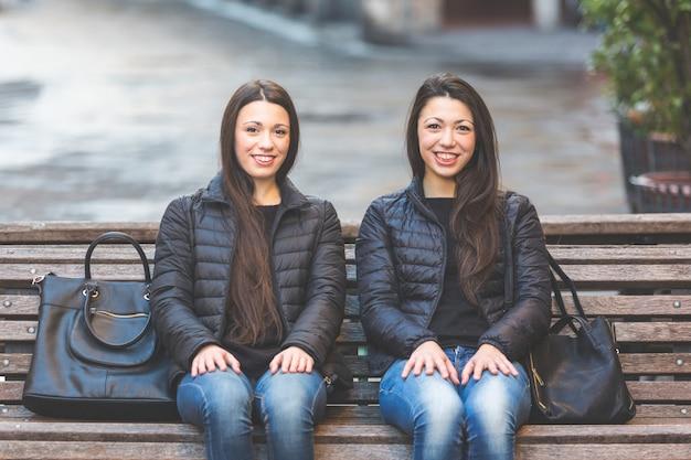 Zwei weibliche zwillinge, die auf einer bank in der stadt sitzen