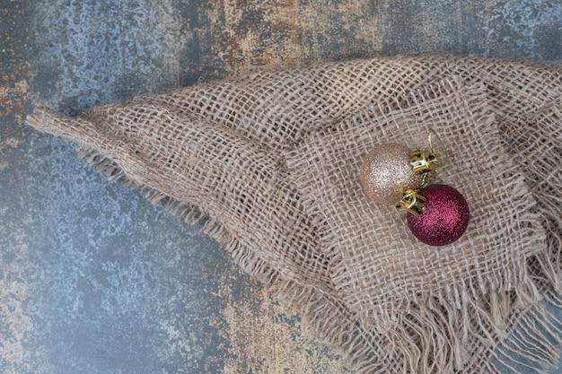 Zwei weihnachtliche glitzernde kugeln auf sackleinen. hochwertiges foto