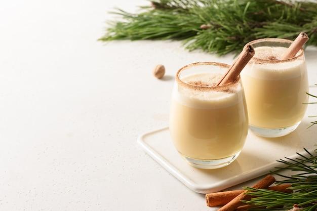 Zwei weihnachts-eierlikör mit geriebenem zimt und muskatnuss auf weißem hintergrund.