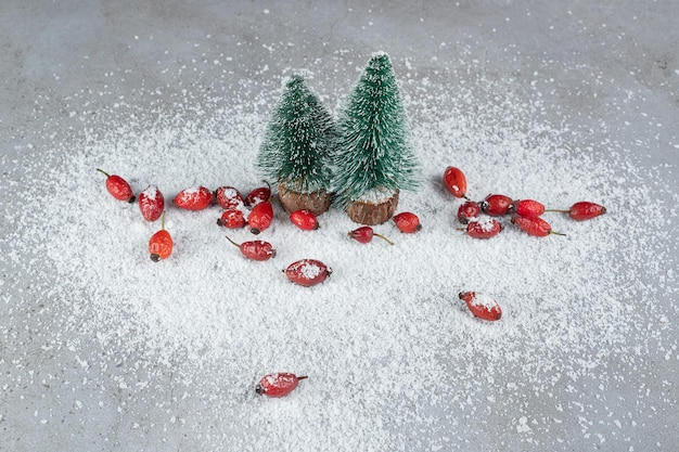 Zwei weihnachtsbaumfiguren und ein bündel hüften auf kokosnusspulver auf marmoroberfläche