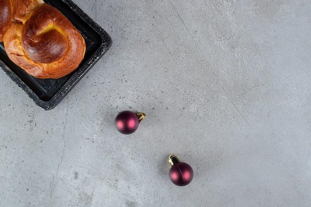 Zwei weihnachtsbaumkugeln aufgereiht mit einem brötchen auf einem tablett auf marmoroberfläche