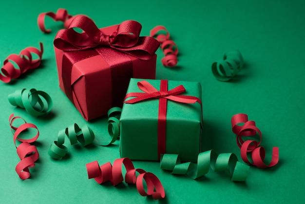 Zwei weihnachtsgeschenke verpackt in rotem und grünem papier mit serpentin auf einem grünen hintergrund draufsicht