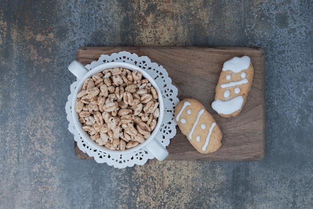 Zwei weihnachtsplätzchen und eine schüssel mit süßen erdnüssen auf holzbrett. hochwertiges foto