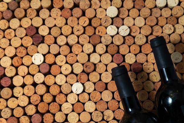 Zwei weinflaschen liegen auf weinkorken, kreativer designhintergrund, platz für text