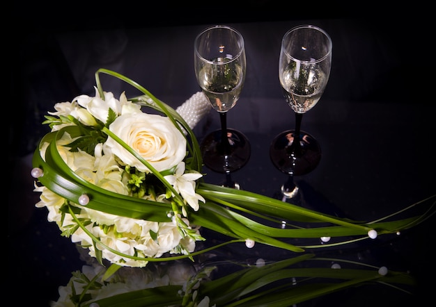 Zwei weingläser champagner und hochzeitsblumenstrauß