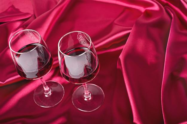 Zwei weingläser mit rotwein auf der roten seide