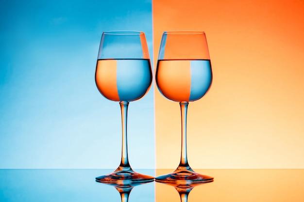 Zwei weingläser mit wasser über blauem und orange hintergrund.