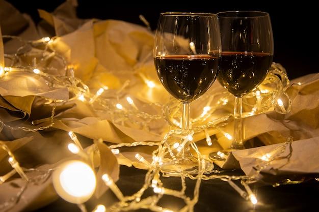 Zwei weingläser stehen in einer leuchtend gelben girlande auf kraftpapier. gemütliche romantische feier...