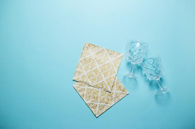Zwei weingläser und goldene servietten auf dem blauen hintergrund. valentinstagkarte auf blauem hintergrund mit kopienraum.