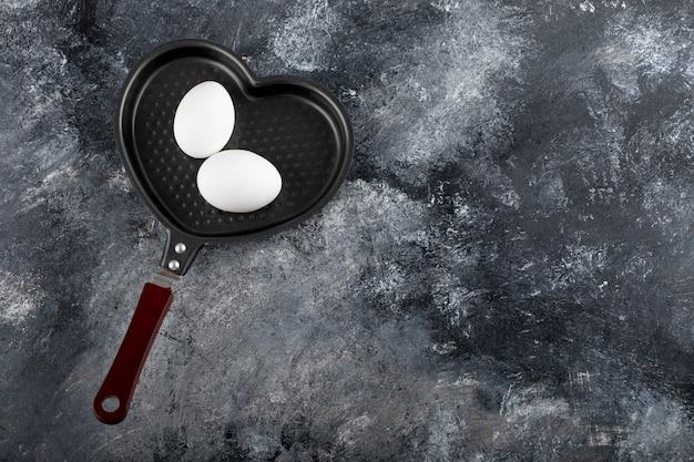 Zwei weiße eier auf herzförmiger pfanne.