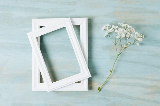Zwei weiße grenzrahmen mit babyatemzugblume auf hölzernem hintergrund der beschaffenheit