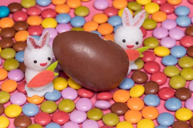 Zwei weiße häschen mit schokoladenosterei auf bunten edelsteinsüßigkeiten