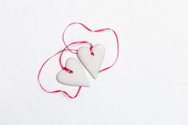 Zwei weiße herzen zusammen mit rosa band auf weißem feiertagskonzept für hochzeit, valentinstag, romantische beziehung. flach mit kopierraum liegen