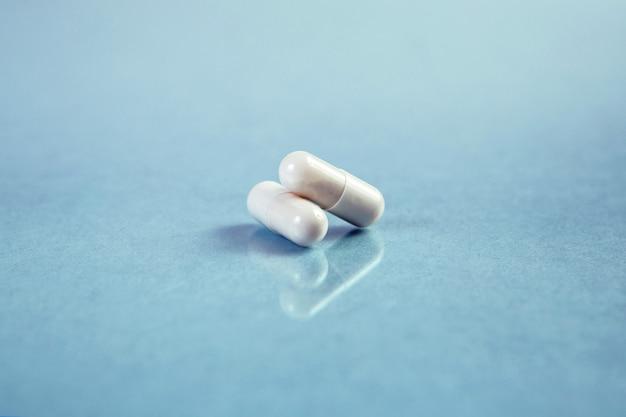 Zwei weiße kapseln auf blauem hintergrund. dosis von verschreibungspflichtigen kapseln.