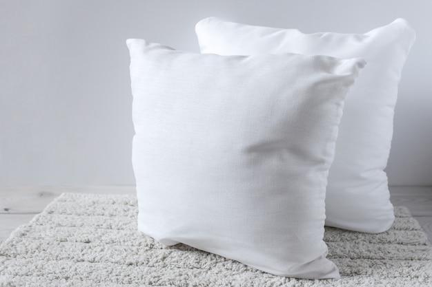 Zwei weiße kissen auf einem flauschigen teppich.