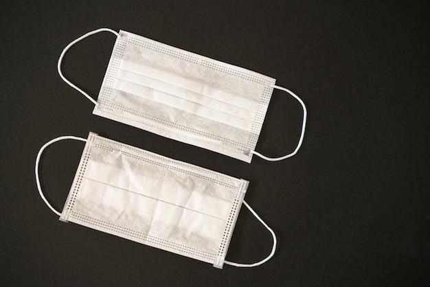 Zwei weiße medizinische masken auf einem schwarzen tisch