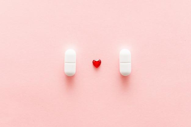 Zwei weiße pillen auf rosa hintergrund mit roter herzform, herzmedikamenten oder weiblichem heilungskonzept