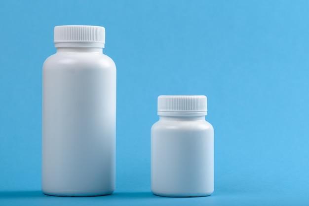 Zwei weiße plastikflaschen auf blauem hintergrund für marke und text