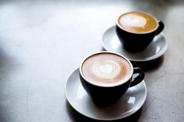 Zwei weiße tassen leckerer cappuccino mit herz-kunst-latte. konkreter grauer hintergrund.