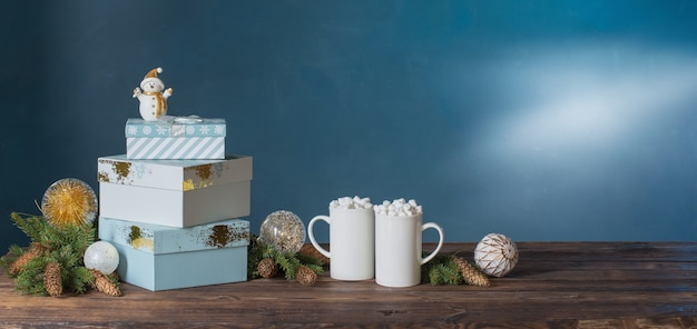 Zwei weiße tassen mit getränken mit marshmallows und weihnachtsdekorationen auf dunklem hintergrund
