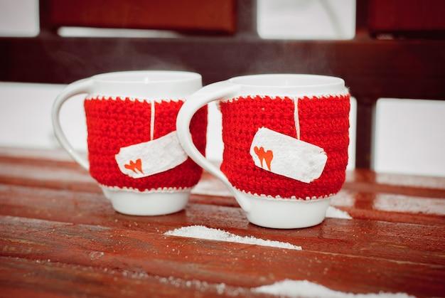 Zwei weiße tassen mit heißem tee oder kaffee in gestrickter kleidung. die tassen dampfen. valentinstag, dekor