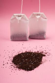 Zwei weiße teebeutel aus papier und eine handvoll schwarzer tee auf einer rosa hintergrundnahaufnahme.