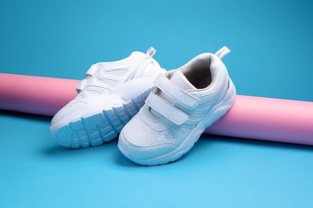 Zwei weiße teenie-sneaker mit klettverschluss für bequemes schuhwerk auf einer rosa langen papierrolle auf ...