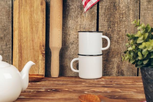 Zwei weiße weinleseteebecher und -teekanne auf küchenarbeitsplatte
