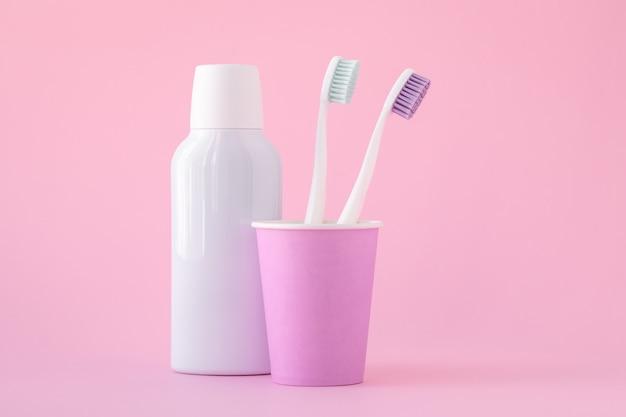 Zwei weiße zahnbürsten in einer rosa tasse und kosmetisches mundwasser in der flasche. prävention von zahnkrankheiten und mundgeruch. mundhygiene, zahnhygienekonzept.