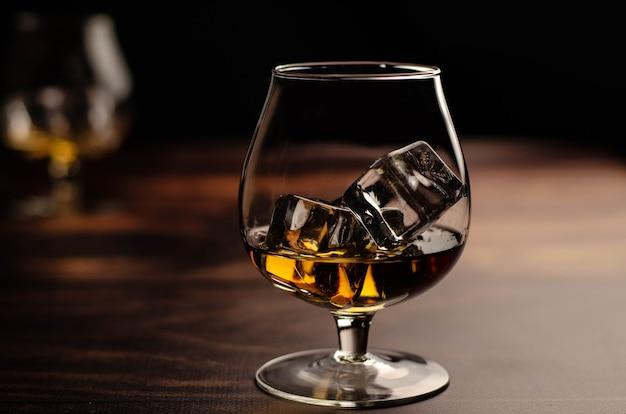 Zwei whisky / cognac-gläser mit eis auf holz