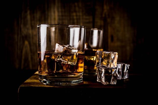 Zwei whisky-schnapsgläser auf dunklem holztisch, mit eiswürfeln,