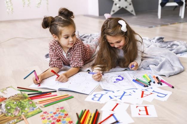 Zwei winzige glückliche mädchen, die in dem malbuch zeichnen, das auf dem boden auf der decke liegt und buchstaben lernt