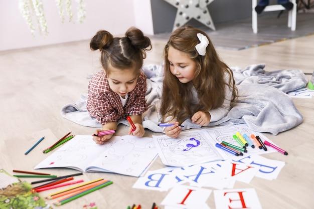 Zwei winzige süße mädchen, die in dem malbuch zeichnen, das auf dem boden auf der decke liegt und buchstaben lernt